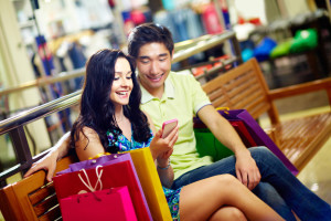 man and woman using mobile phone while shopping